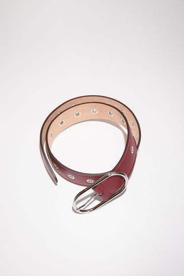 Acne Studios burgundy leather belt is studded with silver-tone metal eyelets along the length and has a discreet engraved logo on the oval-shaped buckle.