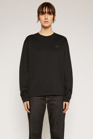 Acne Studios black t-shirt is crafted from lightweight cotton jersey to a relaxed shape with a round neck and long sleeves and accented with a tonal face-embroidered patch on the chest.