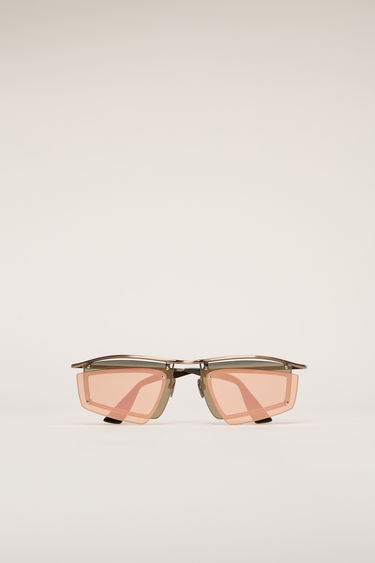 Acne Studios gold/pink sunglasses are crafted with a shield metal frame set with a double-layered tinted lenses and then finished with discreet logo lettering at the temple.