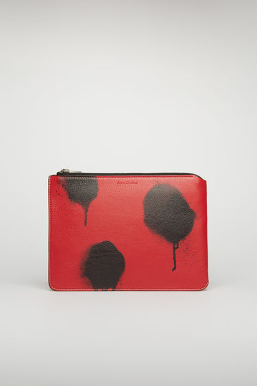 Acne Studios red/black document holder is crafted from grain leather and features a graffiti-style print on the front. It's secured with a silver-tone metal zip and finished with an embossed logo on the top.