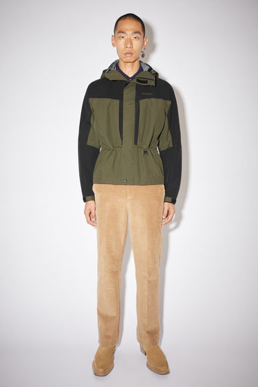 Acne Studios cedar green/black colour block hooded jacket is made is made of a three layer nylon fabric with a technical membrane at the inside the jacket has water proof seams and Acne Studios branding at the chest.