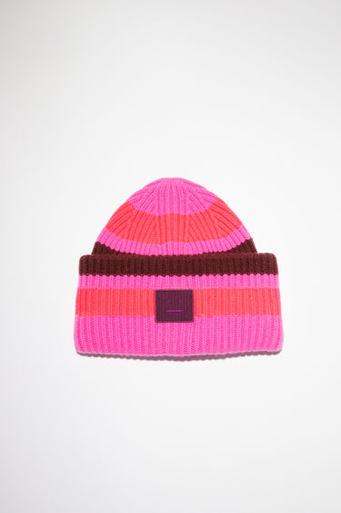 Acne Studios pink/burgundy striped beanie hat is made from rib knit wool with a face logo patch.
