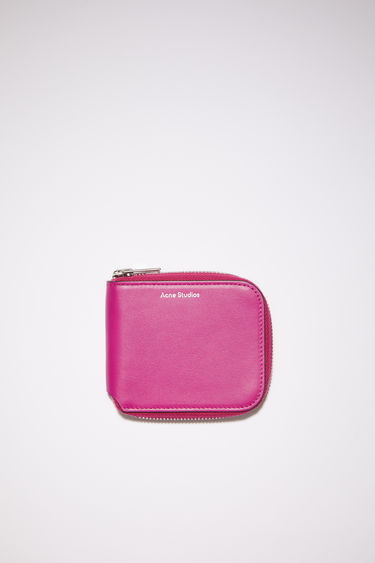 Acne Studios fuchsia pink compact zip wallet is made of smooth leather with two card slots, a bill sleeve, and a zipper closure.