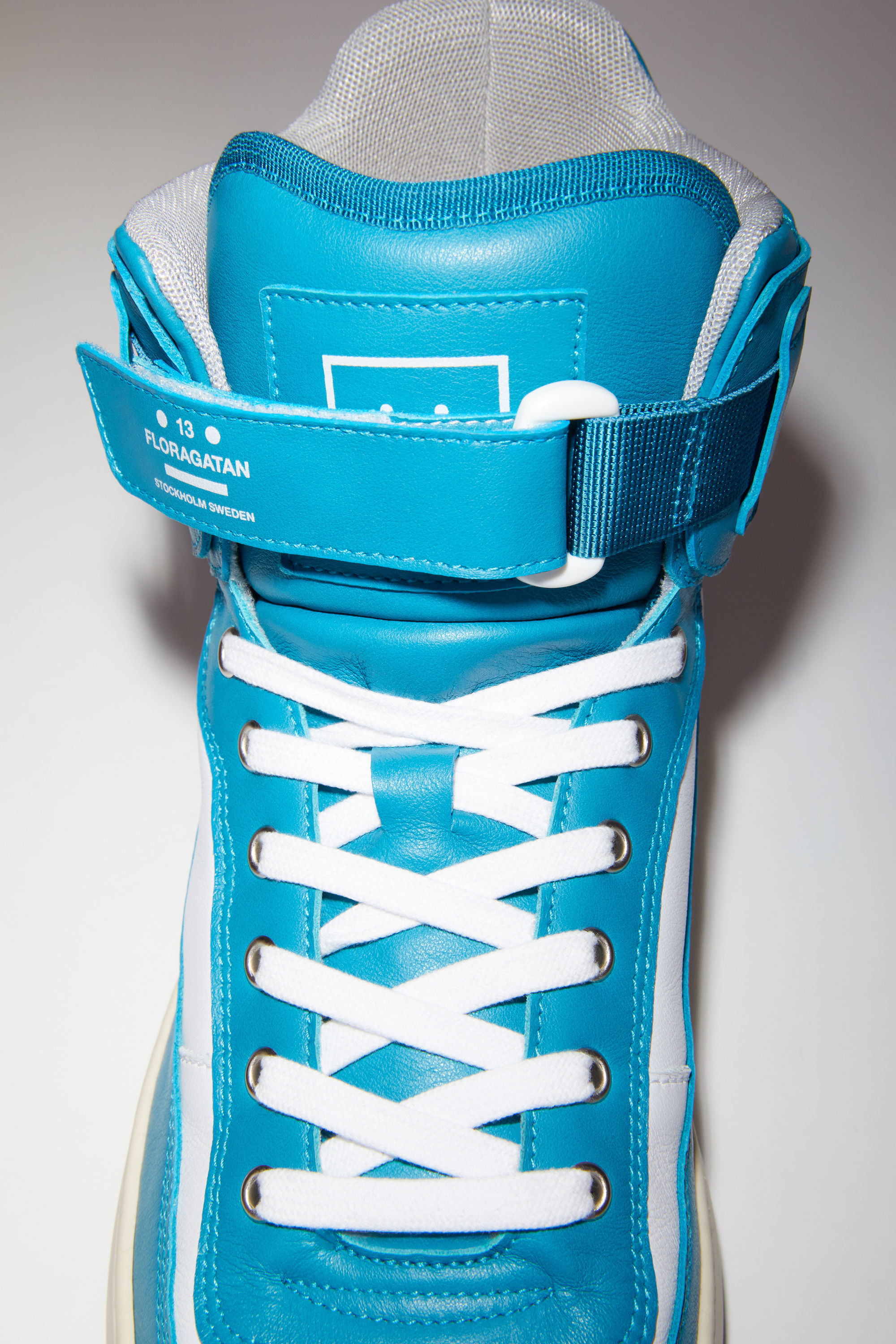 Acne Studios turquoise/white/white lace-up high top sneakers are made of calf leather with a face motif on the back sole. 006