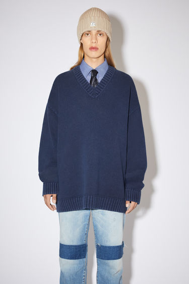 Acne Studios navy v-neck sweater is made of a cotton blend with ribbed accents, washed for a distressed look.