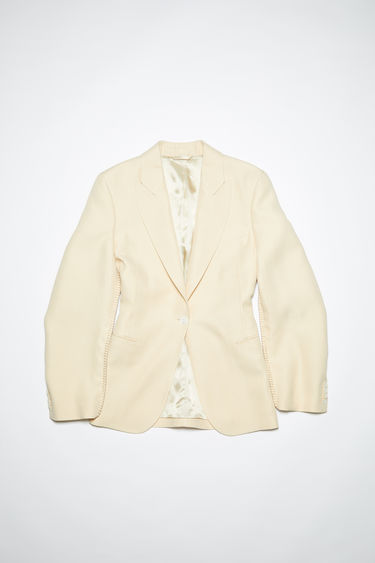 Acne Studios cream beige suit jacket is crafted to a single-breasted silhouette with peak lapels and accented with whipstitched seams.