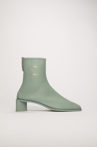 Acne Studios pastel green boots are crafted to a slim silhouette from supple leather and set on a stacked block heel. They are accented with a silver-tone metal zip and a stamped logo on the ankle.