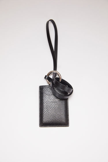 Acne Studios black lanyard card holder is made of calf leather with two card slots and a silver stamped logo on the front.