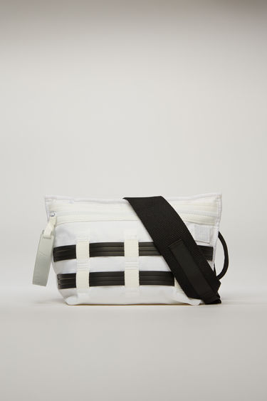 Acne Studios white/black belt bag is crafted from ripstop and detailed with flat rubber cords woven on the front. It is equipped with a front zip pocket, mesh pocket, and an adjustable buckled strap.
