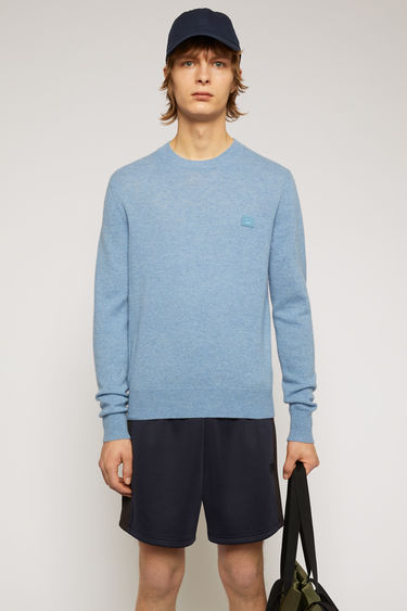 Acne Studios mineral blue sweater is knitted in a fine gauge from soft wool yarns and accented with a tonal face-embroidered patch on the chest.