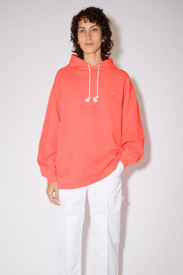 Acne Studios electric pink oversized hooded sweatshirt is made of a organic cotton blend with a face logo patch and ribbed details.