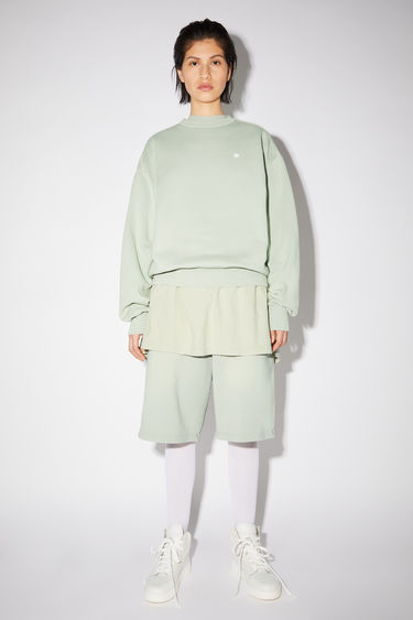 Acne Studios dusty green relaxed bubble fit sweatshirt is made of organic cotton with a contrasting face patch and embroidery.