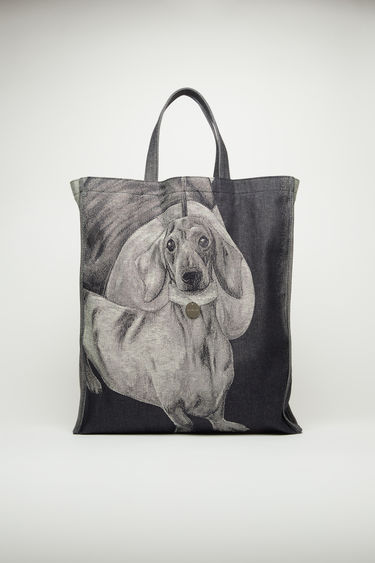Acne Studios indigo blue tote bag is crafted from rigid denim and features a dachshund jacquard and a branded metal tag created by British artist Lydia Blakeley.