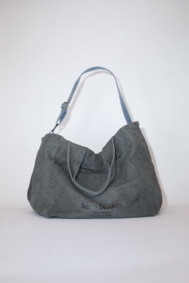 Acne Studios dark grey large shopper bag is made of cotton with a printed Acne Studios logo on the front.