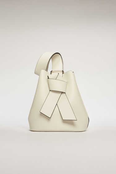 Acne Studios Musubi white/black bucket bag features a twisted knot inspired by the formation of traditional Japanese obi sash. It's crafted from soft grain leather with a matte finish and has a detachable zip pouch to store small essentials.