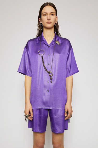 Acne Studios electric purple satin shirt is cut to a boxy silhouette with an open collar and short sleeves and finished with tonal buttons through the front.