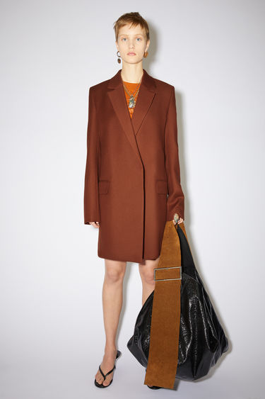 Acne Studios cognac brown double-breasted coat is made of a wool blend with hidden closures.