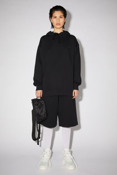Acne Studios black oversized hooded sweatshirt is made of organic cotton with a face logo patch and ribbed details.