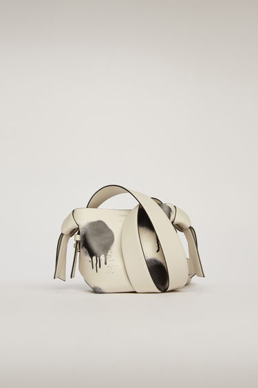 Acne Studios Musubi Micro white/black bag is made from soft grain leather and features a graffiti-style print on the body of the bag. It's accented with a twisted knot along each side of the bag.