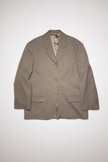 Acne Studios taupe grey single-breasted suit jacket is made of a wool blend with a very oversized fit.