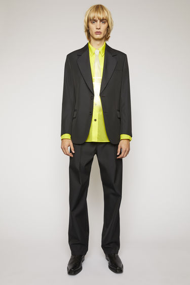 Acne Studios black suit jacket is constructed with padded shoulders and wide lapels and features two ring button closures and neatly pressed creases on front darts.