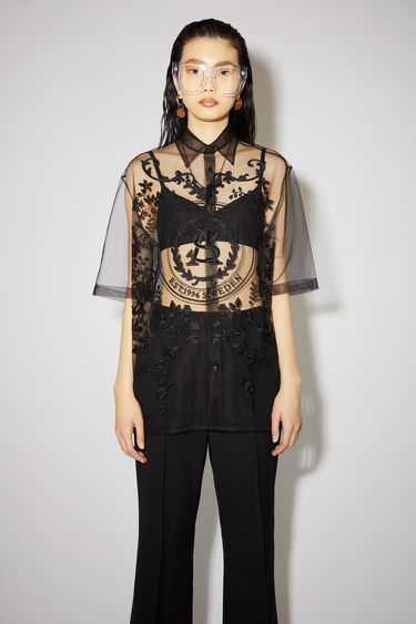 Acne Studios black relaxed fit blouse is made of embroidered tulle with button closures.