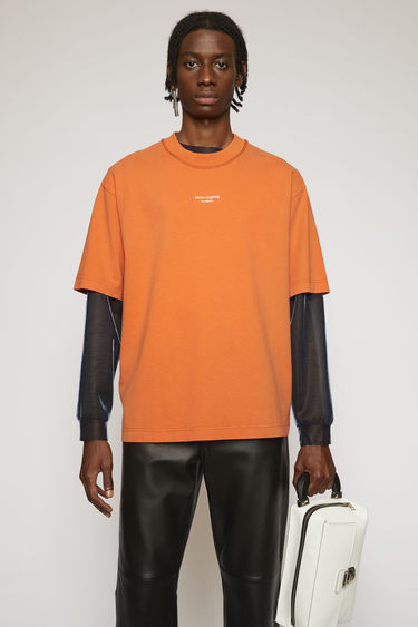 Acne Studios mandarin orange t-shirt is cut from midweight cotton jersey to a boxy silhouette and then accented with a reversed logo across the chest.