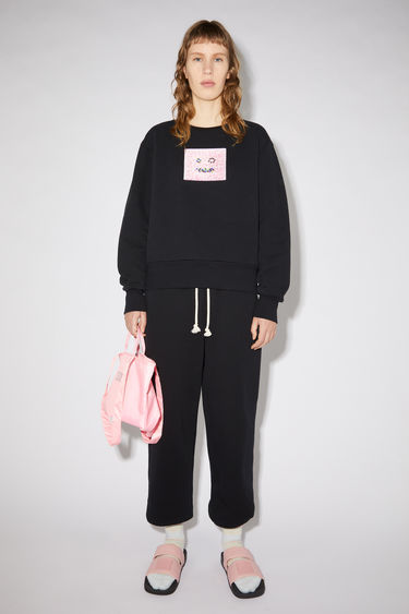 Acne Studios black regular fit crew neck sweatshirt features a beaded face detail on the front.