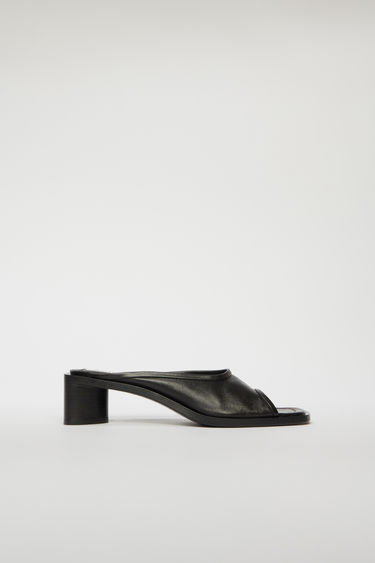 Acne Studios black/black mules are crafted from supple leather with wide straps and then set on a triangular block heel.