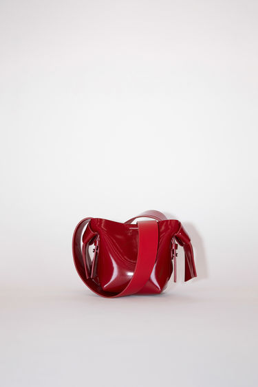 Acne Studios dark red small patent bag features twisted knots inspired by traditional Japanese obi sashes. It has a debossed logo, magnetic closure, and detachable strap with handles for wear as either a shoulder or handbag.