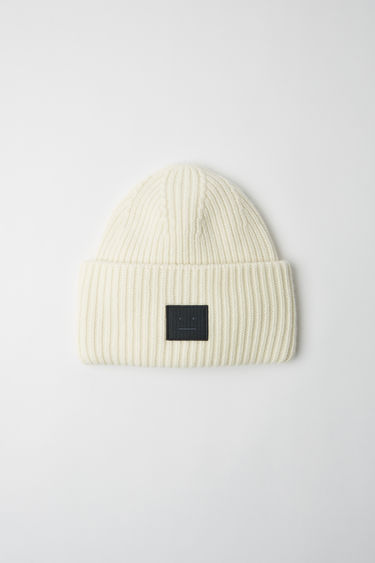 Acne Studios white beanie is rib-knitted from soft wool and accented with a face-embroidered patch on the front.