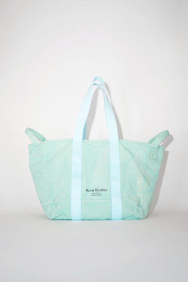 Acne Studios mint green canvas tote bag is made of cotton with webbing shoulder straps and carrying handles.