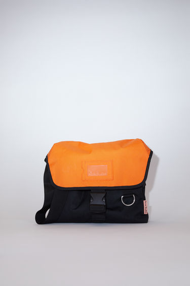 Acne Studios black/orange large, durable messenger bag has a clear vinyl ID pocket, strap with decorative stitching, and an Acne Studios logo tab.