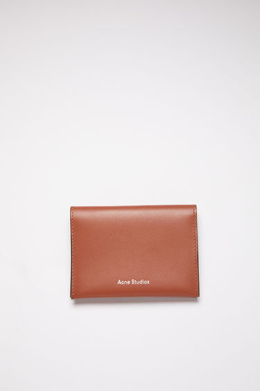 Acne Studios almond brown bifold card holder is made of soft grained leather with four card slots and a silver stamped logo on the front.