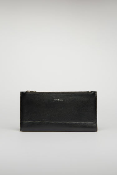 Acne Studios black continental wallet features a smooth leather construction and it opens to reveal 12 card slots, a zipped pocket and two notes compartment.