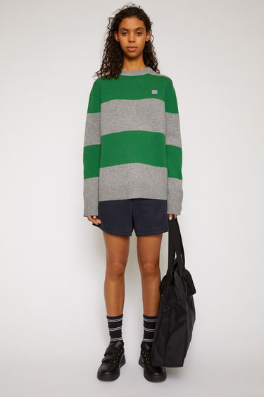 Acne Studios grey melange/deep green wool sweater is knitted in a relaxed shape with block stripes and accented with a face-embroidered patch on the chest.