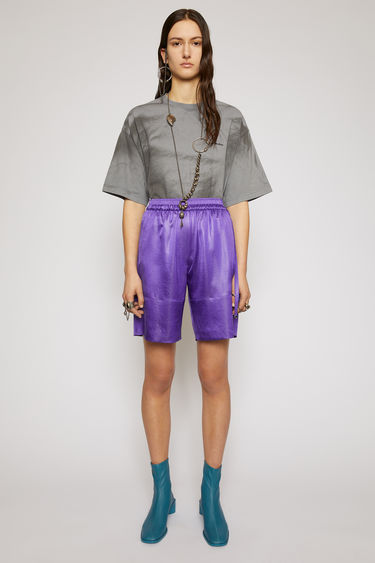 Acne Studios electric purple satin shorts are tailored in a straight-leg shape that drapes loosely over the leg and finished with an elasticated waistband with drawstrings on the side.