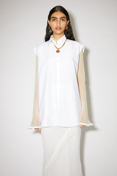 Acne Studios white sleeveless shirt is made of a cotton blend with a relaxed fit.