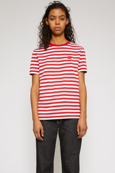Acne Studios cherry red t-shirt is cut from lightweight cotton jersey that's patterned with breton stripes and features a tonal face-embroidered patch on the chest.