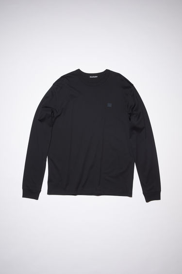 Acne Studios black relaxed fit long sleeve t-shirt is made of organic cotton with an embroidered tonal face patch.