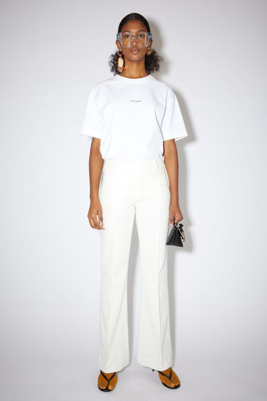 Acne Studios off white suit trousers are made of cotton with a boot cut fit.