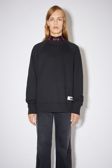 Acne Studios black/black raglan sleeve sweatshirt is made of a cotton blend with a label at the bottom side.