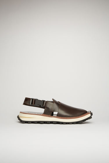 Acne Studios brown/black sandals are inspired by traditional Peshawari Chappal. They're crafted from high-shine leather with wide cross-over straps and set on a stacked tread sole.