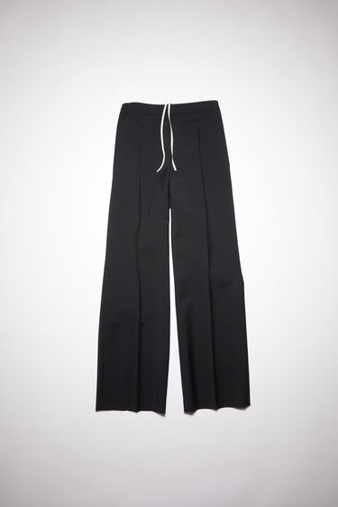 Acne Studios black trousers are tailored in a straight-leg shape with an elasticated waistband and has a faux front placket and neatly pressed creases.