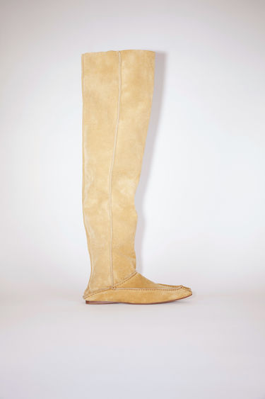 Acne Studios beige tall, slip-on boots are made of calf suede leather, inspired by Moroccan babouche slippers.