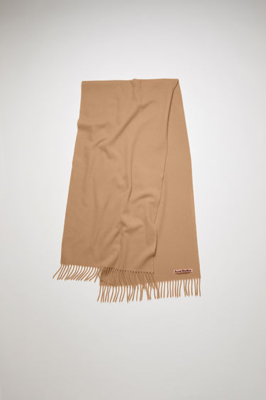 Acne Studios camel brown narrow fringed scarf is crafted from pure wool and finished with a label across one corner.