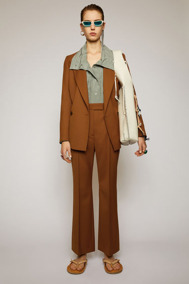 Acne Studios cognac brown wool-blend trousers are cut slim through the hips and fall into cropped, kick-flare legs with stitched pressed creases through the front.