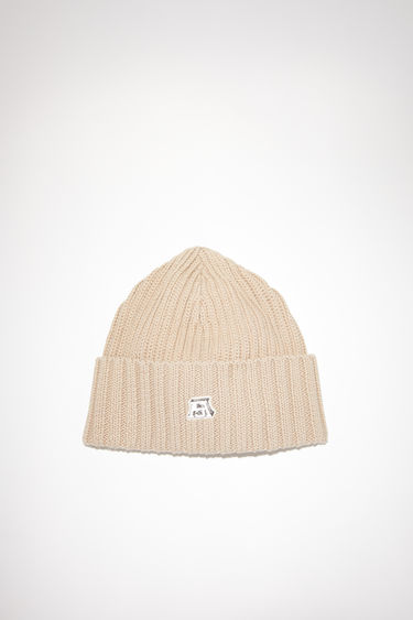 Acne Studios hazel beige rib knit beanie hat is made of a cotton blend with an upturned edge and embroidered patch at the front.