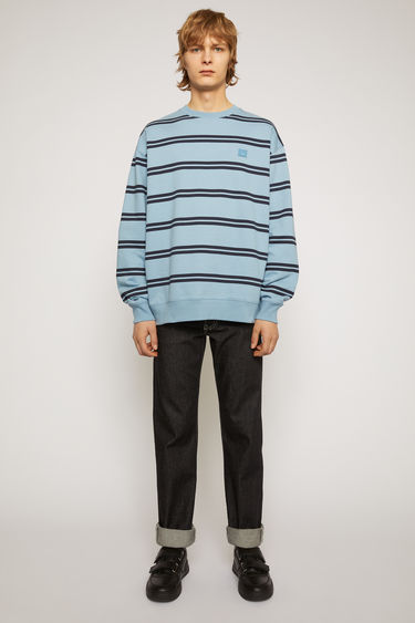 Acne Studios mineral blue oversized sweatshirt is crafted from lightweight loopback jersey that's patterned with double stripes and accented with a tonal face-embroidered patch on the chest.