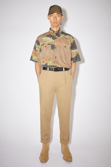 Acne Studios sand beige casual structured trousers are made of a cotton blend with a slight stretch and a tapered fit.